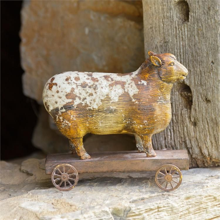 "This Vintage Sheep Toy reproduction features an aged wood appearance with chippy white paint, giving it a well-worn timeless feel. Made of resin, with a wood cart and metal wheels, it makes the perfect farmhouse accent for any room. The old wheel cart is reminiscent of vintage children's toys such that you may find tucked away in an antique shop. 7""W x 5.5""H"