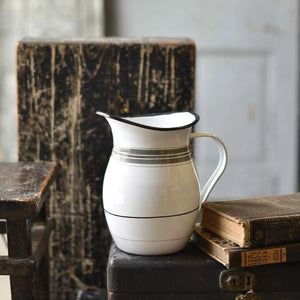 "Farmhouse decor isn't complete with at least one enamel pitcher. This Enamel Pitcher with Vintage Stripes offers a decorative twist with its stripe pattern inspired by vintage fabrics. This white enamel pitcher has black trim and a generous spout. Not food safe.  7.5""H"