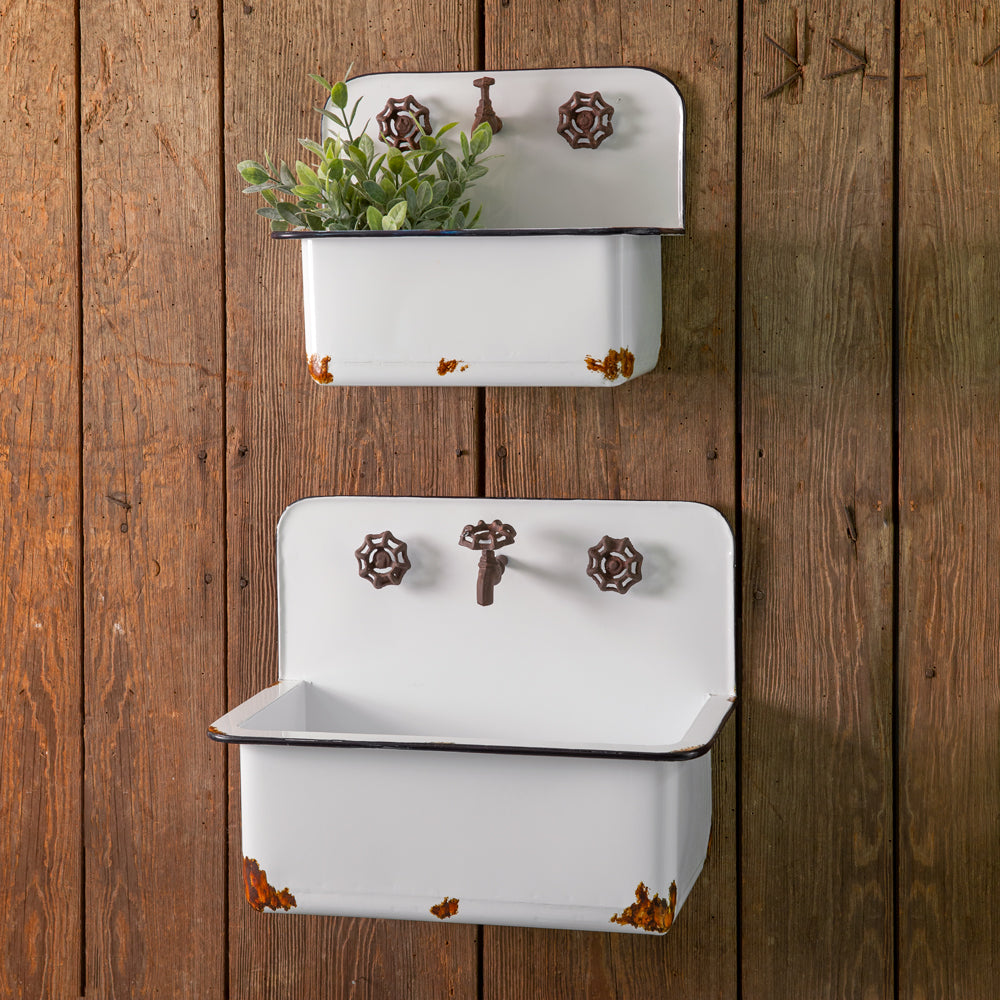 It's easy to love the look of old enamel farmhouse sinks. They just have a nostalgic quality that instantly transports any farmhouse kitchen or bath to a simpler time. These Vintage Enamel Style Sink Planters let you capture that old-fashioned essence without having to call the plumber. Made of metal with an aged enamel style finish, each wall sink planter features a rusty spigot or faucet and faux hot and cold knobs.
