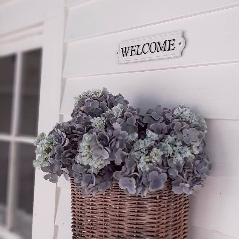 "Give your guests a warm welcome with this Vintage Style Welcome Sign. Inspired by vintage enamel signs, this sturdy cast iron sign is white with raised black lettering and trim. (hardware not included.) 8.65""L x 2.15""H"