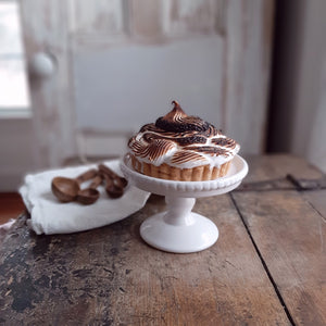 "Give tarts, cupcakes, muffins and more the spotlight they deserve with this White Beaded Mini Cake Stand. This ceramic stand makes everything look even sweeter. It also makes a perfect pedestal for candles and other accents. 5""Diam x 3.75""H"