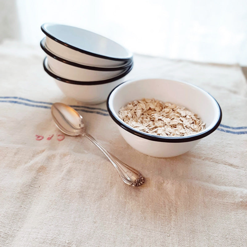 "These White Enamel Bowls are perfect for adding vintage farmhouse style to your kitchen. This set of four white enamel bowls includes black rims to emulate those found in antique shops. Their size makes them perfect for morning cereal, for gathering up all your ingredients while you're cooking, or use them to hold condiments and dipping sauces. Item is food, oven and dishwasher safe. Measures 2¾"" high by 5¼"" in diameter."