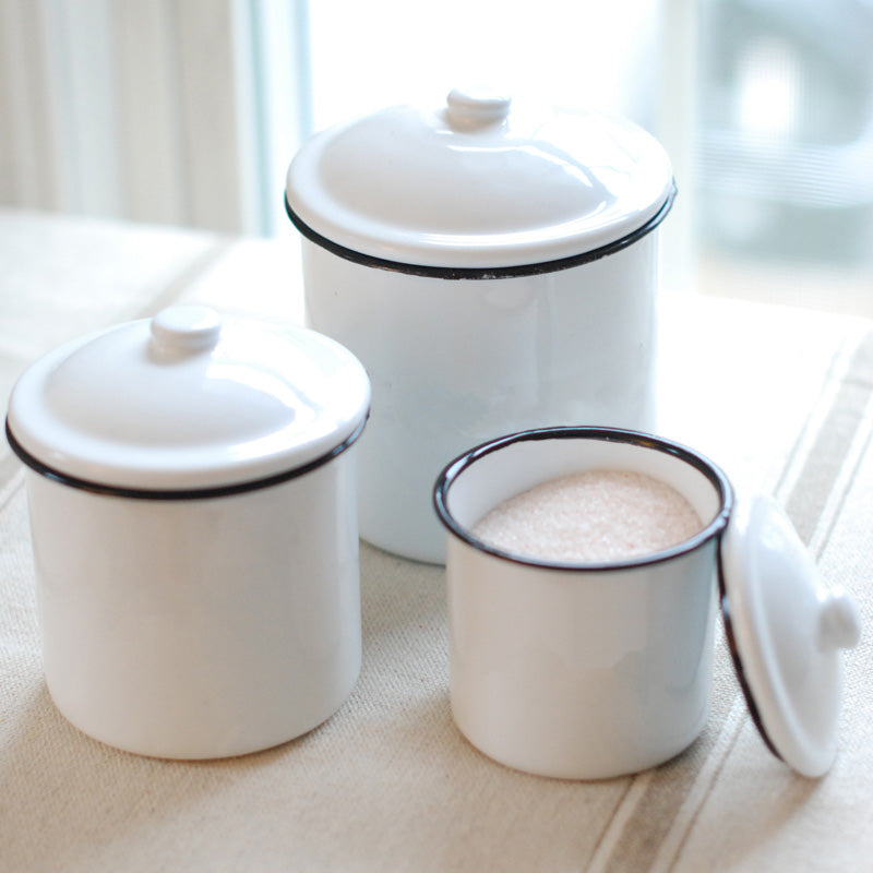 This set of three White Enamel Canisters with Black Trim has nostalgic charm, reminiscent of grandma's kitchen. The set's retro style is perfect for farmhouse kitchens, and features distressed white enamel with black trim. Canisters are food, oven and dishwasher safe.