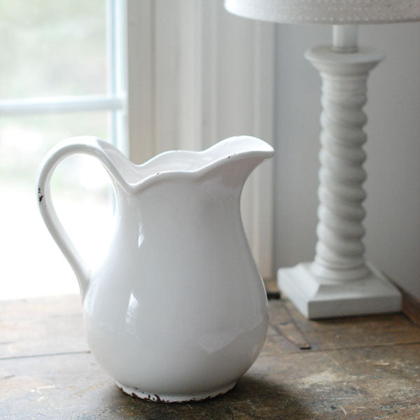 "Reminiscent of old ironstone pitchers that would be used along with basins, our White Farmhouse Stoneware Pitcher has a graceful design. Features an aged crackle finish with shabby chic style. Create a beautiful farm table centerpiece with your favorite flowers. 6"" Base X 8.25""W X 9""H"