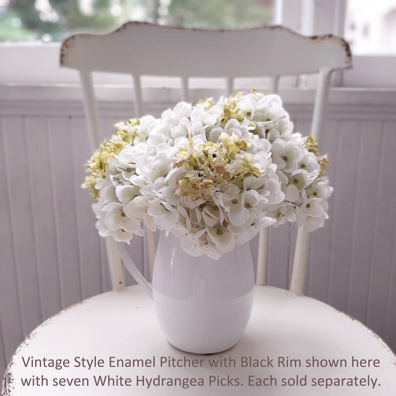 "Our Creamy White Hydrangea Pick is a sweet summer floral made of fabric petals. This is a young blossom with hints of pink and fresh chartreuse on a green plastic stem. It has a large faux leaf jutting from the stem and looks charming as is or combined into a floral arrangement. It easily fits into baskets, buckets, and milk cans and more. 9"" high by approx 5.5"" wide by 5.5"" deep."