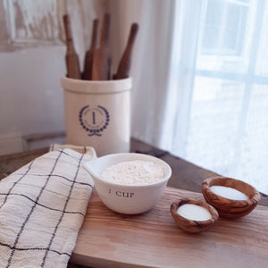 White Measuring Cup shown with olive wood cutting board and nesting bowls, stonware crock and farmhouse kitchen towel