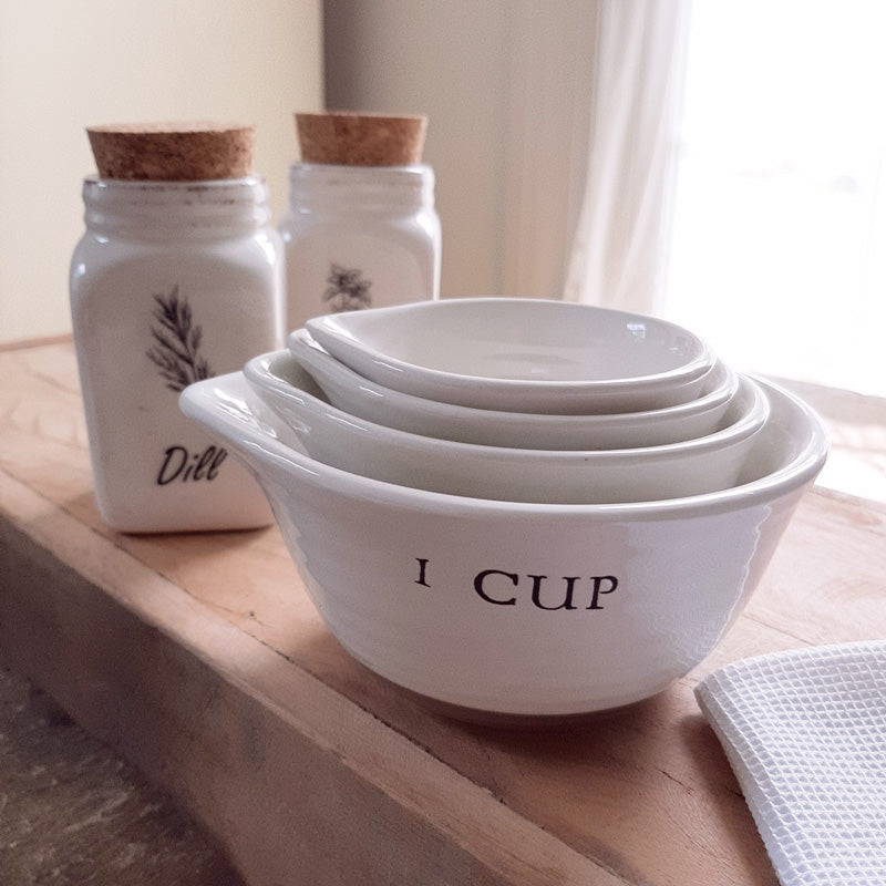 The perfect tool for any farmhouse kitchen, this set of four Antique White Nesting Measuring Cups features a duo tone finish, with creamy white on top and a rustic mauve detail along the bottom edge. Each cup has a spout for easy pouring and the cup size embossed on the side. Set of four includes 1 cup, 1/2 cup,  1/3 Cup and 1/4 cup. Microwave, dishwasher and oven safe.