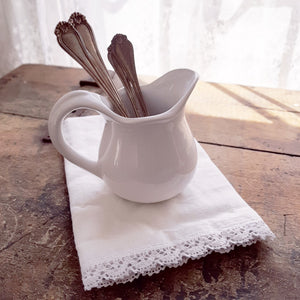 "Reminiscent of old ironstone pitchers that would be used along with basins, our White Stoneware Creamer has a graceful design. Makes a beautiful accent to any sideboard or shelf.  4""H"