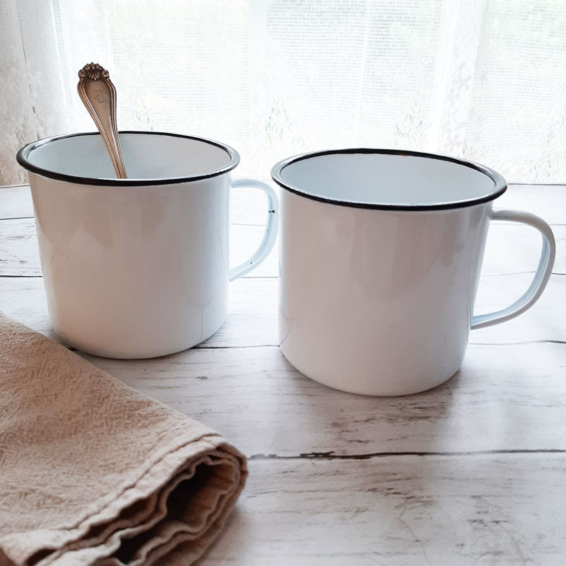 "Add vintage style to your farmhouse kitchen with these oversized White Enamel Soup Mugs with Black Rims. These mugs are a country classic, and they're perfect for coffee, soups, hot chocolate and more. Enamelware is the ideal choice for picnics or camping. Set of two. Item is food, oven and dishwasher safe. Measures 4"" high by 4¼"" wide. Do not microwave."