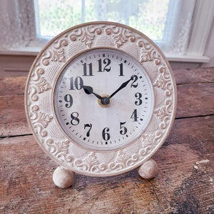 "There's a natural elegance to this Whitewash Wood Table Clock. The beautiful, detailed carvings pop off of the natural wood backing, while the whitewash finish lends a soft touch. This charming clock is perfect for a desk or side table.  Requires 1 AA battery (not included). 6""D"