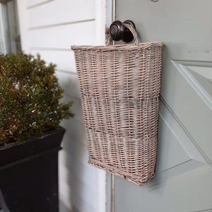 Nothing says country cottage style quite like this hanging Willow Door Basket. Perfect for any season. Fill it with your favorite flowers or greenery, and welcome guests with this eye-catching basket. It also comes in handy when gathering long-stem flowers from the garden. Includes a handle (also made of willow) at the top for hanging.