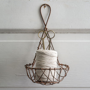 "This sweet Wire Basket Twine Holder with Scissors looks as though it belongs in an English country garden potting shed. This clever combination of twine and snips, so you have everything you need all in one place is Yankee ingenuity at its best! The vintage style metal hanging twine basket comes with twine and scissors. It can hang or sit on a table. The large loop at the top of the item allows for easy mounting to a wall. It measures 5""W x 5""D x 8""H."