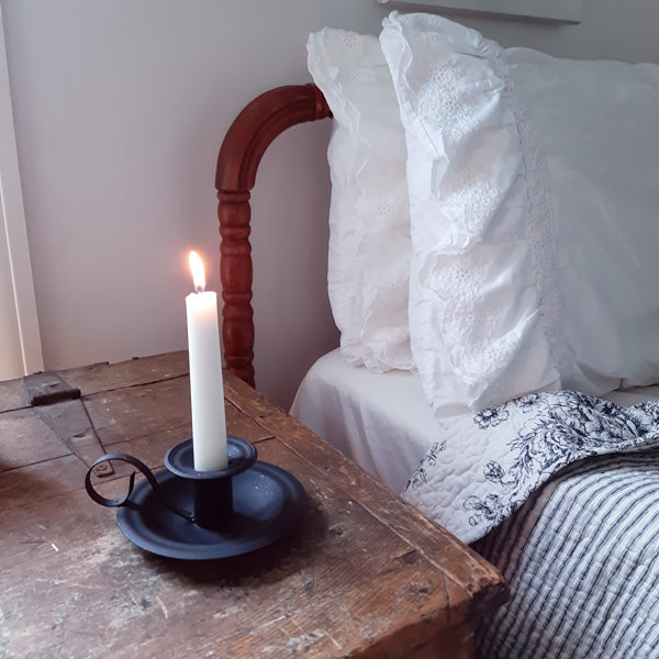"Inspired by 18th-century colonial style candle holders, our Wyeth Chamberstick Taper Holder features an aged metal finish with flecks of brown for a time-worn feel. It has the classic finger loop and tray, which made it easy to carry candles from room to room. Taper candle not included. This piece makes a simple yet elegant accent to any room in your farmhouse. 5""W x 2""H"