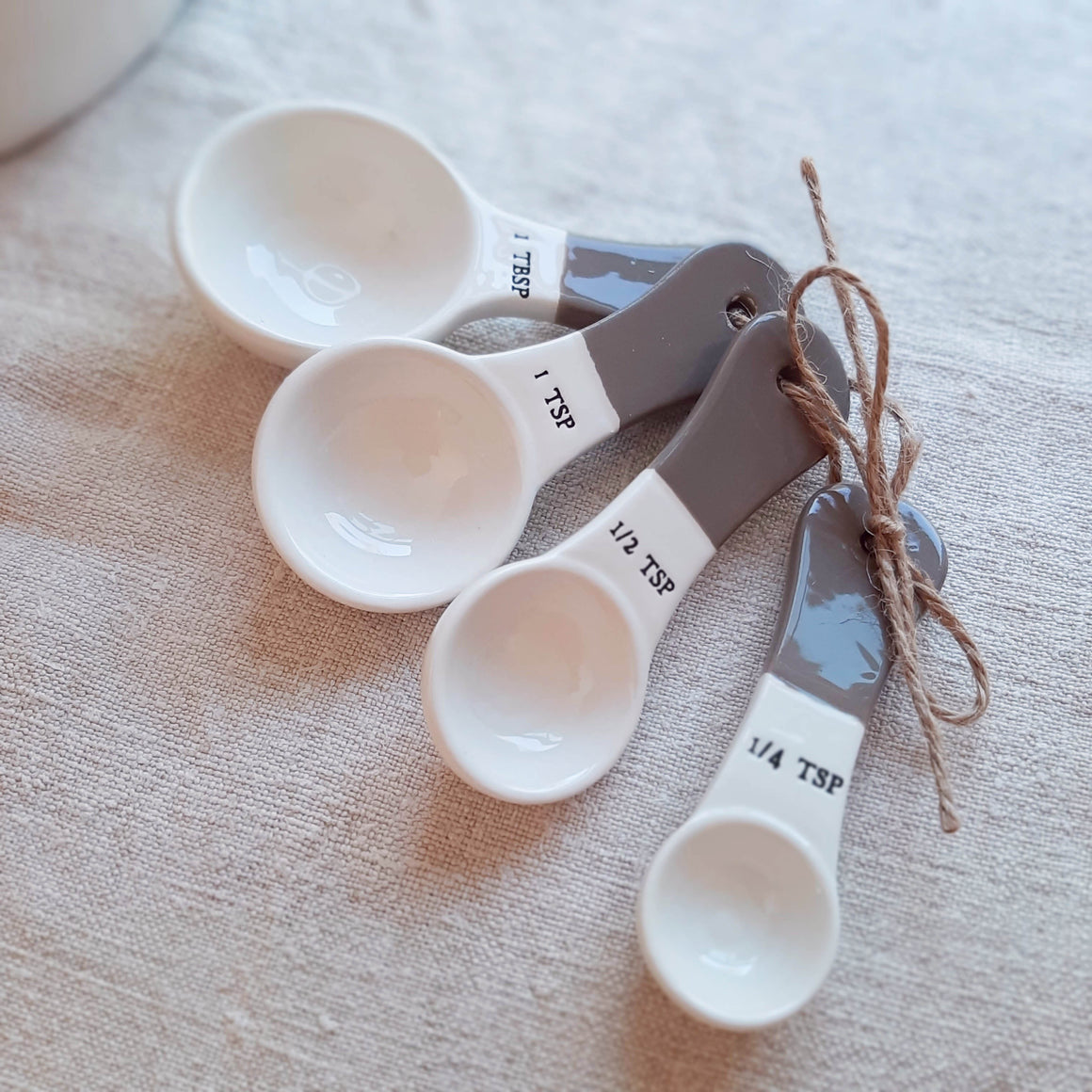 The perfect companion for any farmhouse chef, this set of four Ceramic Measuring Spoons features a duo tone finish, with creamy white on top and a rustic mauve detail along the bottom edge. Each spoon has the measurment embossed on the side. Set of four includes 1 TBS, 1 TSP, 1/2 TSP,  1/4 TSP. Microwave, dishwasher and oven safe.