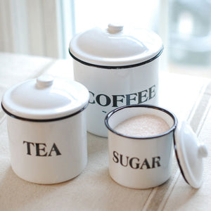 These vintage style Enamel Coffee, Tea, Sugar Canisters have nostalgic charm, reminiscent of grandma's kitchen. The set's retro style is perfect for farmhouse kitchens, and features white enamel canisters with the words Coffee, Tea, and Sugar in black and metal lids with black trim.