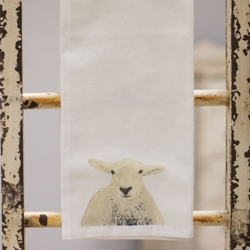 "The sweet little sheep face on this 100% cotton Sheep Tea Towel will brighten your farmhouse kitchen. Features a lightly-distressed screen printing of a sheep for a time-worn, vintage feel. Turn this charming tea-towel into an over-sized napkin for rustic farmhouse entertaining or hang from a stylish hook by the attached fabric hanger on the reverse side. 19""L x 28""H"