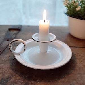 "Add that centuries old farmhouse look to any bedside bureau or tabletop with our White Chamberstick Taper Candle Holder. It has the classic finger loop and tray, which made it easy to carry candles from room to room back in the day. The white enamel finish adds a sweet cottage feel. Taper candle not included.  5""W x 2½""H"
