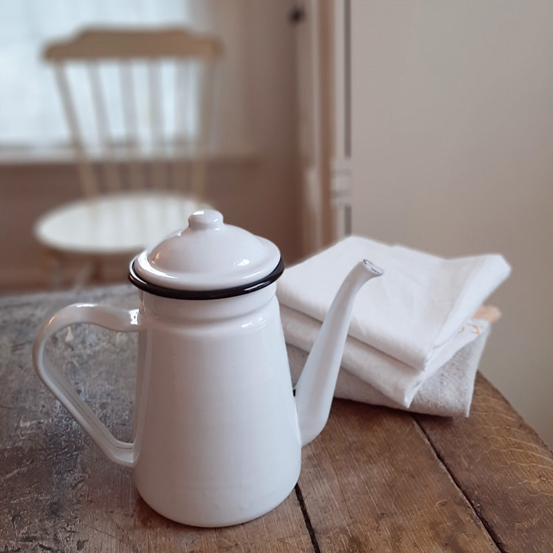 "Add a bit of vintage charm to your coffee station with this White Enamelware Kettle. The goose neck spout and white enamel with black trim offers old-fashioned style. Includes a matching lid. Item is food, oven and dishwasher safe. Do not microwave. 8""W (with handle) x 7.5""H"