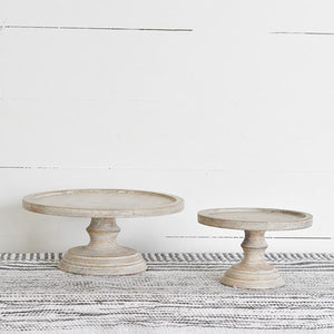 These Whitewash Wood Cake Riser Pedestals bring a touch elegance to your farmhouse entertaining. Show off cakes and cookies or use this versatile cake stand as pedestal to display your favorite objects with farmhouse style. This piece contains imperfections in both the wood and the distressed whitewash finish, making up its rustic charm. A food-safe liner is required if used with food.