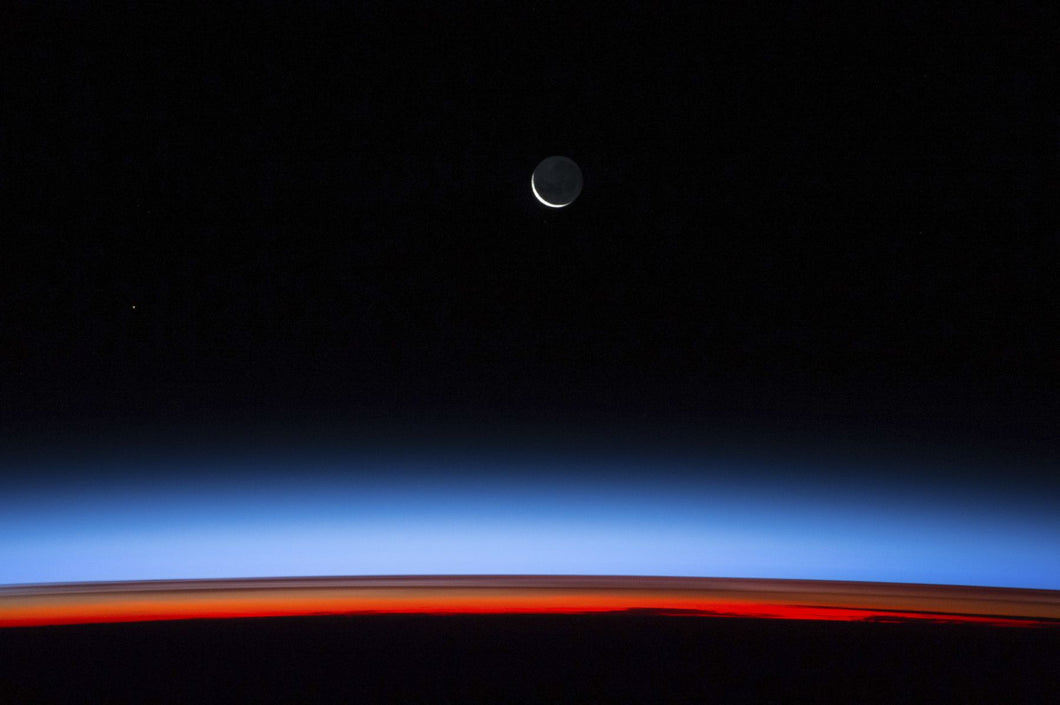 Satellite view of planet Earth showing sunset over Indian Ocean area with crescent moon in the sky