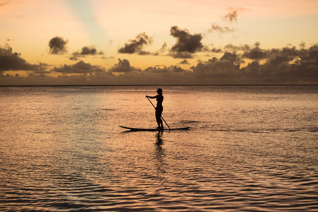 Silhouette of woman paddleboarding in the Pacific Ocean, Bora Bora, Society Islands, French Polynesia