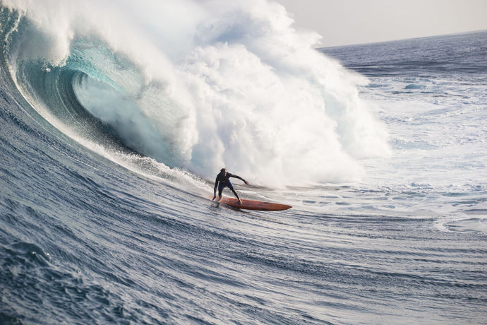 Male surfer surfing wave in Pacific Ocean, Peahi, Hawaii, USA