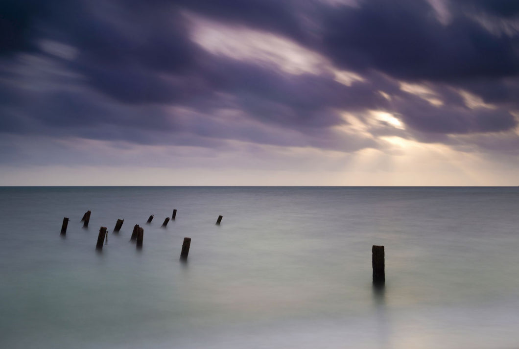 Wooden posts in sea under stormy sky at sunrise, Placencia, Stann Creek, Belize