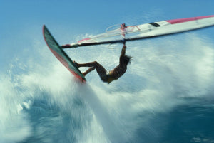 Windsurfer jumping over wave