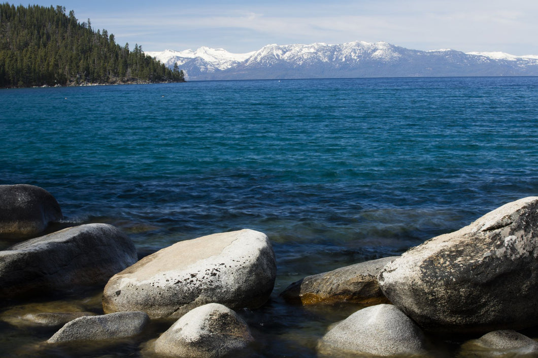 Rocks in a lake with mountain range in the background, Lake Tahoe, California, USA