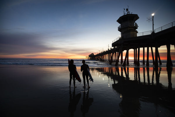 Silhouettes of surfers at Huntington Beach Pier at sunset, California, USA