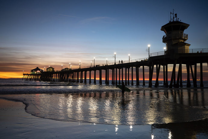 Silhouette of surfer at Huntington Beach Pier at sunset, California, USA