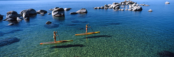 Two women paddle boarding in a lake, Lake Tahoe, California, USA