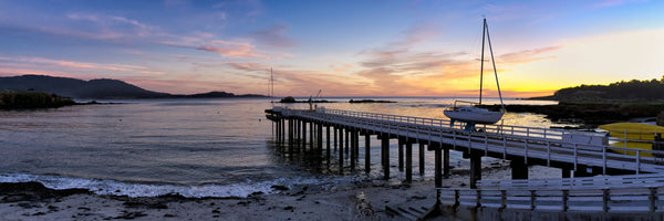 Pier and sailboat at sunset on Stillwater Cove, Pebble Beach, California, USA