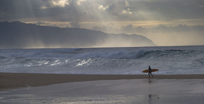 Surfer walking on the beach, Hawaii, USA