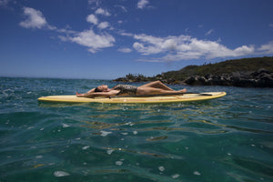 Woman relaxing on paddleboard in Pacific Ocean, Hawaii, USA