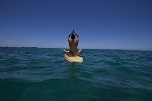 Rear view of woman sitting on paddleboard doing yoga, Hawaii, USA