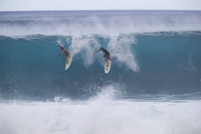 Surfers surfing down a wave on beach, Hawaii, USA