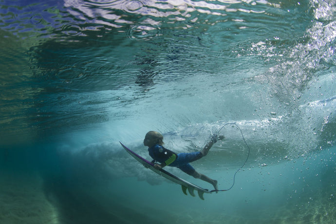 Underwater view of a surfer duck diving in ocean, Hawaii, USA