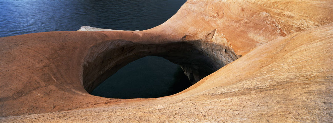 High angle view of a pothole arch at a lakeside, Lake Powell, Utah, USA