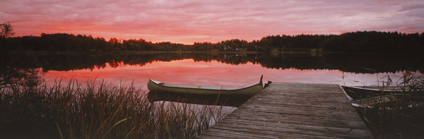 Canoe tied to dock on a small lake at sunset, Sweden