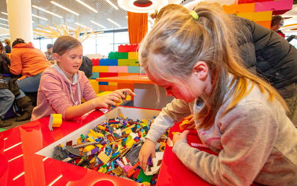 Girls playing at LEGO Tables at Imagination Station