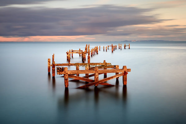 WOODEN PIER POSTS IN CALM BLUE WATER