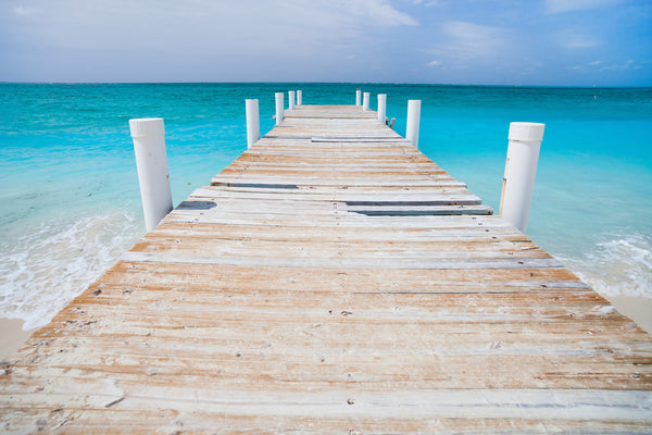 LIGHT COLORED WOODEN PIER ON TURQUOISE WATER