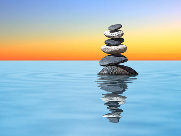 STONES ABOVE CALM BLUE WATER WITH GOLDEN HORIZON