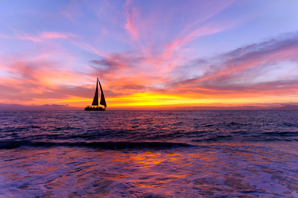 SAILBOAT ON PURPLE WATER AND BLUE SKY AT SUNSET