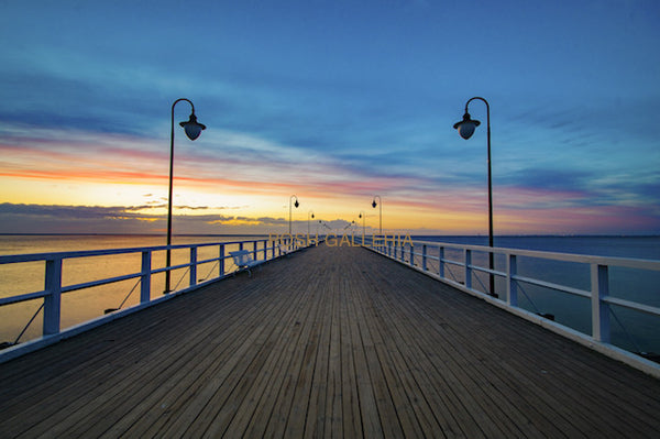 PIER INTO BLUE YELLOW SUNSET