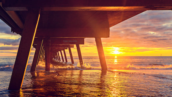 UNDER VIEW OF PIER WITH GOLDEN SUNSET