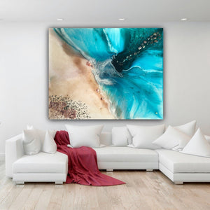 coastal abstract artwork with real shells and stones hanging above white couch
