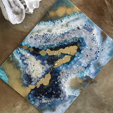 Teal, blue and gold geode artwork on top a brown pelt and next to a geode crystal