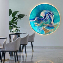 Gold and teal abstract artwork hanging behind table and chairs in contemporary home